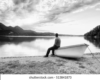 Tired man in red shirt sit on old fishing paddle boat at mountains lake coast. Afternoon sun hidden in clouds above mountain peaks. Black and white photography