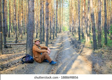 a tired man sat down to rest near a tree on a forest road, a bearded man in a hat. traveler in recovery