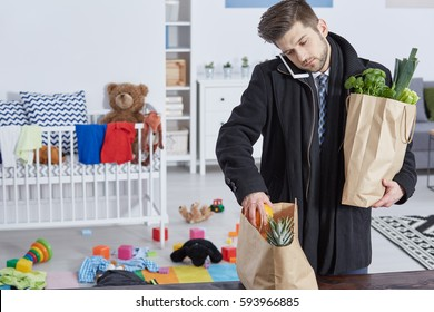 Tired man with shopping bags talking on phone