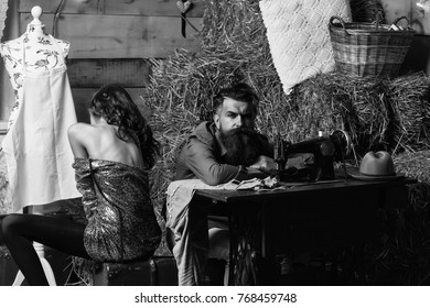 Tired man tailor or dressmaker and pretty girl customer or sexy model with curly brunette hair and undressed back sit near vintage sewing machine in rustic workshop