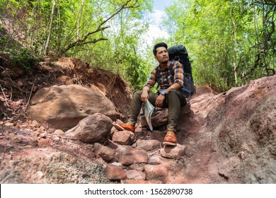 tired man traveler with backpack sitting and resting in the natural forest