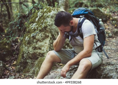 Tired man traveler in wild mountain forest