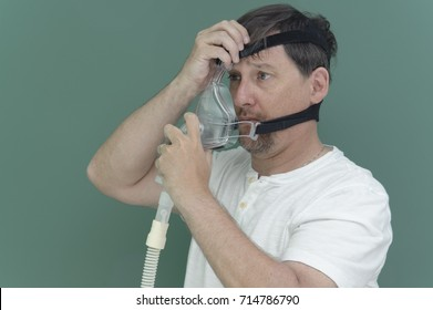 Tired man tries on Cpap mask for the first time.