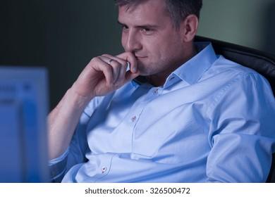 Tired man watching movie during night shift at work