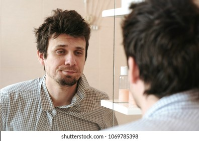 Tired man who has just woken up looks at his reflection in the mirror and sees his scruffy appearance. Straightens his shirt and rubs face with his hand.