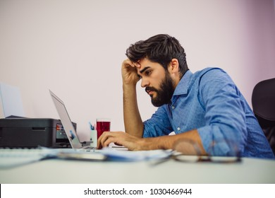 Tired man working on laptop computer.