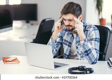 Tired man working on the laptop in the office. Business man wearing casual clothes thinking about a problem at his computer