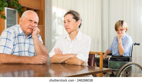 Tired mature couple and disabled person on chair indoor
