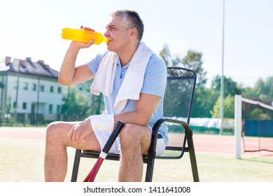 Tired mature man drinking from bottle while sitting on chair at tennis court on sunny day