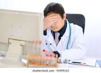 Tired medical doctor working on computer at office
