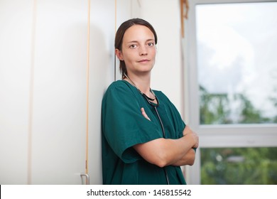 Tired mid adult female surgeon with stethoscope in wall