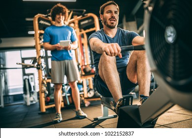 Tired mid adult man using rowing machine for cardio workout in the gym.