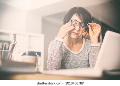 Tired middle age woman rubbing eyes