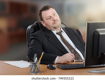 Tired middle aged businessman watches to computer monitor. Pale man wearing black suit sits at wooden office desk. Blurred indoors background. Horizontal shot