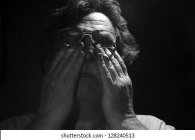 tired middle-aged man rubs his eyes< black and white