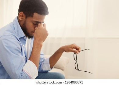 Tired millennial african-american man massaging nose bridge, taking glasses off, having blurry vision or dizziness, copy space