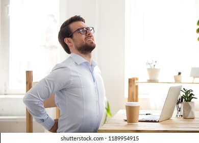 Tired millennial businessman suffering from backache feeling badly, sitting at office desk indoors. Have a back pain, sitting at the computer for a long time, sedentary work and bad posture concept