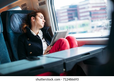 Tired Millennial young woman sleeping on train traveling
