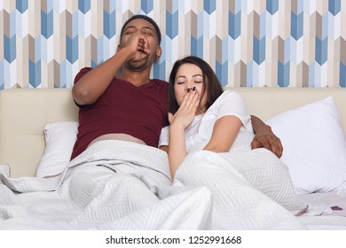 Tired mixed race woman and man yawn as want to sleep, pose in bed against colourful wallpapers. Sleepy international husband and wife awake early in morning, going on work. Bed time concept.