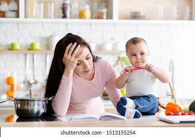 Tired mother holding head, trying to work at home but baby disturbing her, kitchen interior, free space
