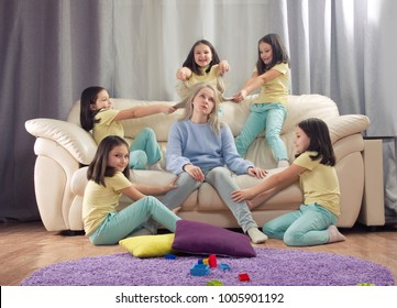 tired mother and many children. Daughter playing with mother, the hair pulling. Mom doesn't want to play with the baby. Depression, children's behaviour, hyperactivity, requires attention.
