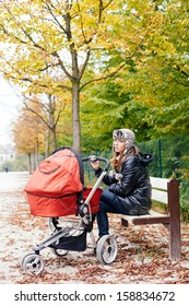 Tired mother sitting on park bench with baby in stroller