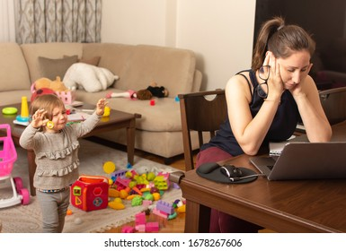 Tired mother trying to work on a laptop at home during her kid crying. Childcare and working mom concept. Women powerful. Toddler tantrum. Young lady working at home during quarantine.