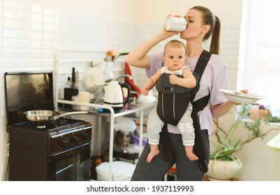 Tired multitasking mother and child in baby carrier. Young girl in the kitchen with a child. The difficulties of motherhood and loneliness. High quality photo