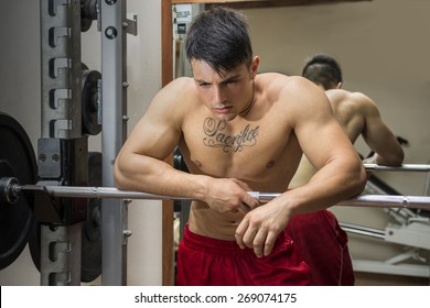 Tired muscular shirtless young male bodybuilder resting on barbell between workouts in gym