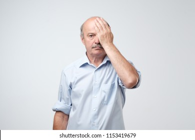 Tired nature european man covering one eye with palm as if having his eyes tested during vision examination. Eyesight problem concept