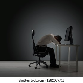 Tired office worker in front of a computer desk