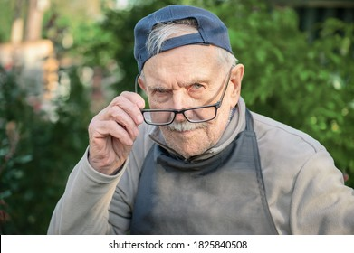 tired old man looks at his interlocutor, adjusts his glasses. The old man can't see very well without his glasses.