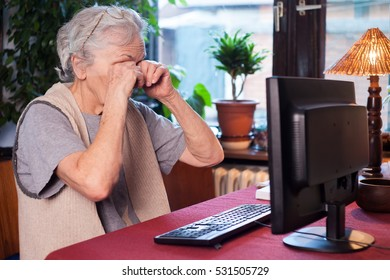 tired old woman sitting in front of the computer
