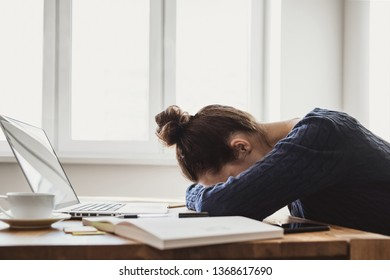 Tired and overworked business woman. Young exhausted girl sleeping on table during her work using laptop, digital tablet and smartphone. Entrepreneur, freelance worker or student in stress concept