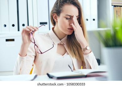 Tired overworked businesswoman in glasses at office covering her face with hand.