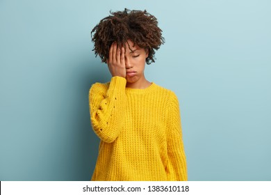 Tired overworked dark skinned girl has sleepy expression, gloomy look, covers face with hand, has eyes shut, gasps from tiredness, wears yellow clothes models over blue background, fatigue after party