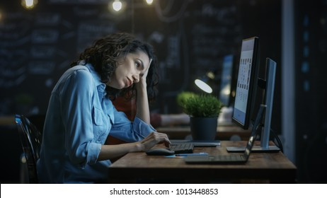 Tired, Overworked Female Financier Holds Her Head in Hands while Working on a Personal Computer. In the Background Creative Office.