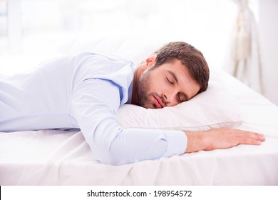 Tired and overworked. Handsome young man in shirt sleeping in bed