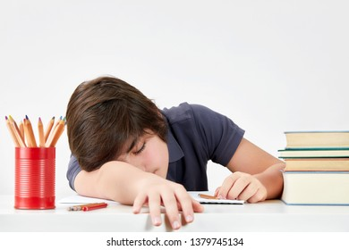 Tired and overworked kid pupil felt asleep at the desk while doing his homework. Concept of hard educational process