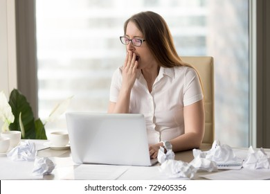 Tired overworked sleepy businesswoman yawning sitting at desk with laptop and crumpled paper, gaping woman feels lack of sleep or chronic fatigue working late after hours, too much paperwork