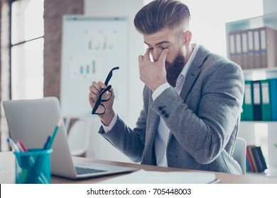 Tired and overworked stylish red bearded manager sitting in front of computer and trying to concentrate, his eyes are dry and hurt