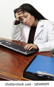 Tired, pensive or stressed doctor with head in hands sitting at computer.