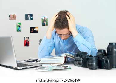 Tired photographer working at his workplace.