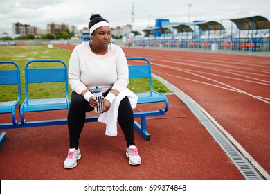 Tired plump female with bottle of water and towel sitting on bench at stadium