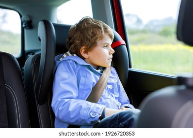 Tired preschool kid boy sitting in car during traffic jam. Sad little school child in safety car seat with belt enjoying trip and jorney. Safe travel with kids and traffic laws concept
