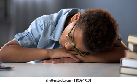 Tired pupil sleeping, sitting at desk, hard educational process, overworked boy