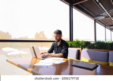 Tired quantity surveyor working at cafe table with diagram and statistic documents. Persistent man dressed in classic black shirt sitting at sofa near green indoor plants. Concept of  preparin