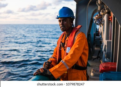 Tired rating Seaman AB or Bosun on deck of vessel or ship , wearing PPE personal protective equipment - helmet, coverall, lifejacket, goggles. Safety at sea. He is tired