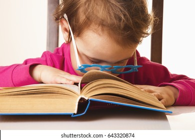 tired of reading little baby girl fell asleep on a book (Knowledge, education, reading, learning concept)