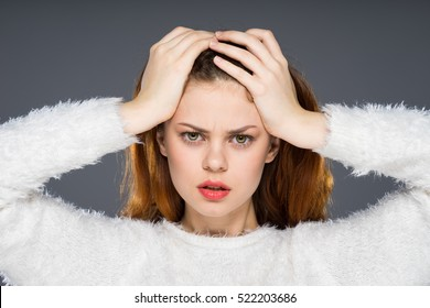 Tired red-haired woman with headache holding her head and angrily looks into the camera. Shocked and upset expression. Hard work concept, brainstorm, many affairs and jobs